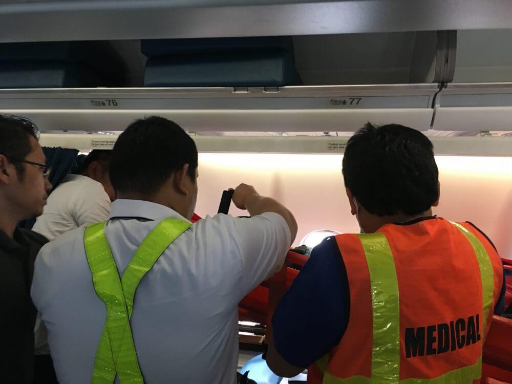 画像はストレッチャーを飛行機の中に運ぶ場面