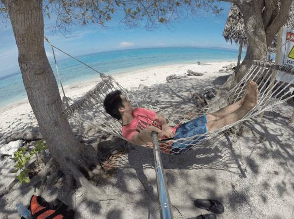 男性がハンモックに揺られながら海を眺めている